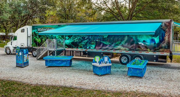 WaterVentures semi truck with awning and activity tables
