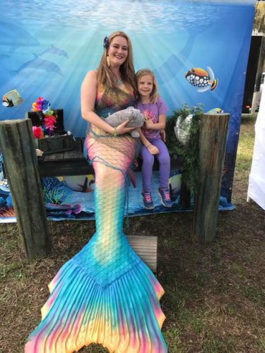 Pretty mermaid woman posing for picture with little girl, photo